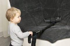 Criança engraçada que limpa o sofá com o aspirador de p30 imagens de stock royalty free