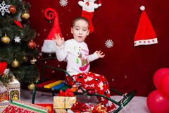 A criança engraçada senta-se em um trenó ao lado de uma árvore de Natal Fotografia de Stock Royalty Free