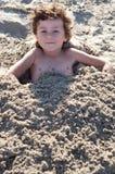 Criança enterrada na areia fotografia de stock