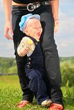 Criança entre os pés da matriz Fotos de Stock Royalty Free