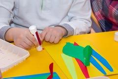 A criança entrega o papel da colagem na classe do mestre da aplicação imagens de stock royalty free