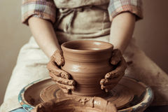 A criança entrega o trabalho na roda da cerâmica na oficina imagem de stock royalty free