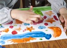 A criança entrega a pintura Foto de Stock Royalty Free