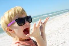 Criança entusiasmado na praia pelo oceano imagens de stock royalty free