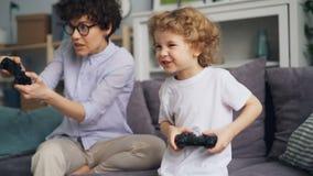 Criança entusiasmado que joga jogos de vídeo com a mamã que sorri e que aprecia a atividade da família
