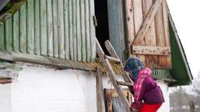 A criança escala acima as escadas no inverno na vila video estoque