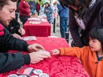 A criança escolhe o selo da mão do voluntário do dia do alimento Imagens de Stock Royalty Free