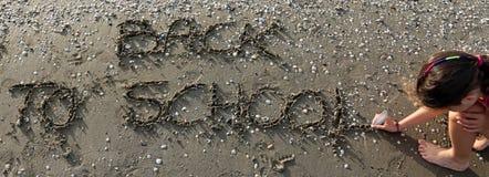 A criança escreve a frase de volta à escola na praia no verão Fotografia de Stock Royalty Free