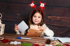 A criança escreve a letra a Santa Claus A menina engraçada no chapéu de Santa escreve a letra a Santa imagem de stock