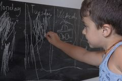 A criança escreve no quadro-negro na escola Foto de Stock Royalty Free