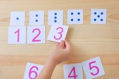 A criança espalha cartões com números aos cartões com pontos O estudo dos números e da matemática Foto de Stock
