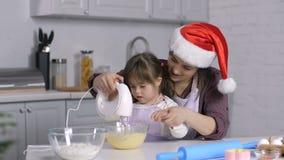 A criança especial das necessidades ajuda a mamã a cozinhar o biscoito do xmas vídeos de arquivo