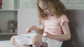 Criança esperta que usa facilmente app móvel na tabuleta, serviços onlines simples no dispositivo vídeos de arquivo