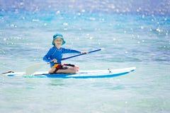 A criança está acima paddleboarding Fotografia de Stock Royalty Free