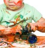 A criança está agarrando alguma pintura usando os dedos Foto de Stock Royalty Free