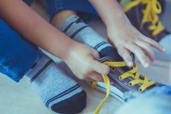 A criança está amarrando laços de sapatas antes que mostra da fase foto de stock