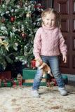 A criança está ao lado de uma árvore de Natal Imagem de Stock Royalty Free