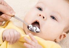 A criança está bebendo o xarope ou a água da medicina Imagens de Stock Royalty Free