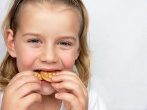 A criança está comendo bolinhos Fotos de Stock Royalty Free