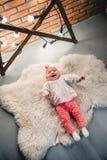A criança está encontrando-se em um tapete de lã e sorri na câmera fotos de stock royalty free