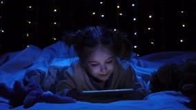 A criança está encontrando-se em uma cama que guarda um portátil e que olha uns desenhos animados Fundo de Bokeh video estoque