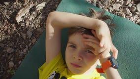 A criança está encontrando-se na terra, a mão está sob sua cabeça video estoque