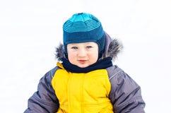 A criança está estando na neve do inverno sobre o fundo natural foto de stock