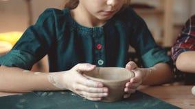 A criança está fazendo uma placa da argila uma lição na cerâmica a menina faz testes padrões em um selo da argila video estoque