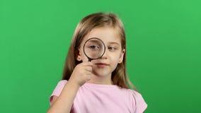A criança está guardando uma lupa Tela verde vídeos de arquivo