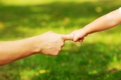 A criança está guardando uma mão dos mans pelo dedo em um verde fora Foto de Stock Royalty Free