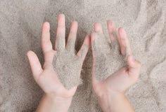 A criança está jogando com a areia do mar Sypet, voando afastado Relaxe, meditação imagem de stock