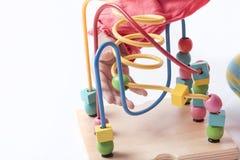 A criança está jogando com formas diferentes dos blocos e está movendo-o aro Fotografia de Stock
