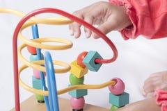 A criança está jogando com formas diferentes dos blocos e está movendo-o aro Foto de Stock Royalty Free