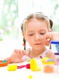 A criança está jogando com massa colorida Fotografia de Stock Royalty Free