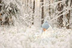 A criança está jogando na neve do inverno imagem de stock royalty free