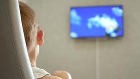 A criança está olhando uns desenhos animados A tela da tevê é fora de foco filme