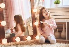 A criança está penteando perto do espelho fotos de stock