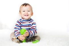 A criança está sentando-se com pesos à disposição Imagem de Stock
