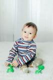 A criança está sentando-se com pesos à disposição Fotografia de Stock Royalty Free