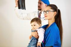 A criança está sentando-se nas mãos do doutor, o segundo doutor olha o raio X Fundo branco imagens de stock