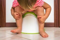A criança está sentando-se no urinol do bebê imagens de stock royalty free