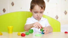 A criança está tendo o divertimento na tabela, close-up, jogando na modelagem multi-colorida do plasticine ou da massa para jogos video estoque