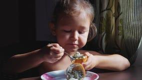 A criança está tendo o retrato do café da manhã de pouca menina bonito come o fruto de paixão filme