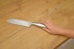 A criança está tentando obter uma faca de cozinha Fotografia de Stock Royalty Free
