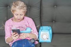 A criança está usando um smartphone fotos de stock
