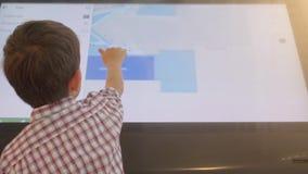 A criança está usando um tela táctil do suporte interativo da informação filme