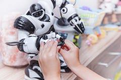 A criança estende uma mão ao robô O conceito da amizade entre o robô e a criança imagens de stock