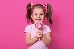 A criança fêmea bonita guarda o pirulito listrado enorme na forma do coração, olha feliz e excitado, veste a camisa cor-de-rosa d foto de stock royalty free