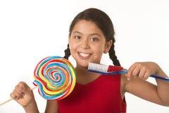 Criança fêmea bonito que guarda doces espirais grandes do pirulito e a escova de dentes enorme no conceito dos cuidados dentários fotos de stock royalty free