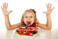 Criança fêmea caucasiano consideravelmente feliz que come o prato completamente dos doces na dieta perigosa do abuso doce do açúc fotografia de stock